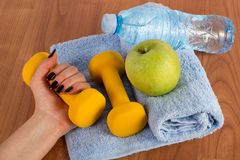 Female hand with yellow dumbbell and fresh green apple and water bottle on blue towel on wooden floor royalty free stock images