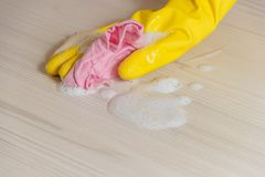 Female Hand in Yellow Glove Cleaning Light Wooden Modern Table with Pink Cloth for Home Maintenance and Housekeeping. Female Hand in Yellow Glove Cleaning Light Royalty Free Stock Image