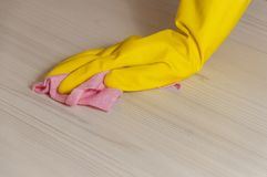 Female Hand in Yellow Glove Cleaning Light Wooden Modern Table with Pink Cloth for Home Maintenance and Housekeeping. Female Hand in Yellow Glove Cleaning Light Stock Images