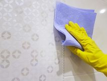 Female hand in yellow gloves washes tile. Female hand in yellow gloves washes the tile Royalty Free Stock Photos