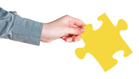 Female hand with yellow puzzle piece Stock Image