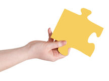 Female hand with yellow puzzle piece Royalty Free Stock Photography