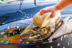 Female hand with yellow sponge washing car Stock Images