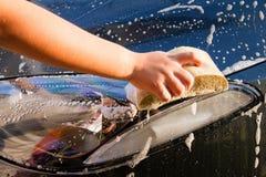 Female hand with yellow sponge washing car Stock Image