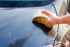 Female hand with yellow sponge washing car Stock Photos