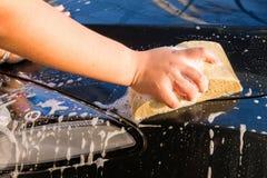 Female hand with yellow sponge washing car Royalty Free Stock Photo