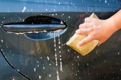 Female hand with yellow sponge washing car Stock Images