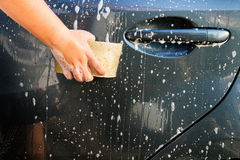 Female hand with yellow sponge washing car Royalty Free Stock Photos