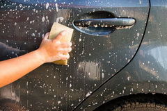 Female hand with yellow sponge washing car Royalty Free Stock Photo