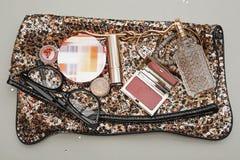 Female handbag with cosmetics. Over grey Royalty Free Stock Image
