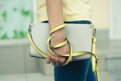 Female handbag gray-yellow in female hands closeup Royalty Free Stock Photos
