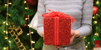 Female handing a red glitter square shape gift box wrapped with red ribbon bow to someone, blurred Christmas tree in background royalty free stock image