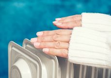 Female hands above the heater. Heating in cold weather royalty free stock images