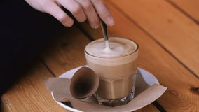 Female hands add sugar refined sugar in a glass of cappuccino on a saucer and stir it. stock video footage