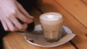Female hands add sugar refined sugar in a glass of cappuccino on a saucer and stir it. Girl hands closeup with glass of coffee stock footage