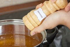 Female hands add to the pot the seasoning. On which is written the word inspiration Stock Photo