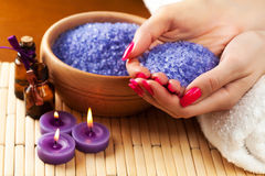 Female hands with aromatic candles and towel. Spa Royalty Free Stock Photography