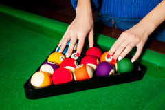 Female hands are arranged billiard balls in triangle Royalty Free Stock Photo
