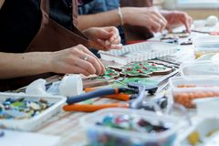 Female hands artist collect mosaic close up. The artist maker mosaic in a wooden harvesting. Female hands closeup collect mosaic of colored stones. Human royalty free stock photos