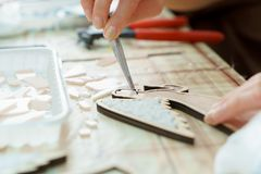 Female hands artist collect mosaic close up. The artist maker mosaic in a wooden harvesting. Female hands closeup collect mosaic of colored stones. Human stock image
