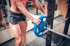 Female hands on athletic barbell Stock Images