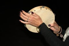 female hands banging the tambourine stock photography