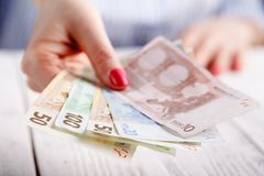 Female hands with banknotes give money Stock Photo