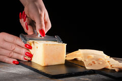 Female hands with beautiful bright manicure cut cheese whetstone by means of a  slicer on  black slate plate Stock Images