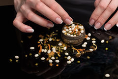 Female hands with beautiful French manicure gather the haricot scattered on a black background, peas, dried vegetables. Female hands with beautiful classical stock photo