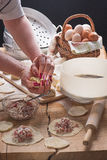 Female hands with beautiful manicure mold pelmeni on a table-top from an oak. In style a rustic Stock Photos