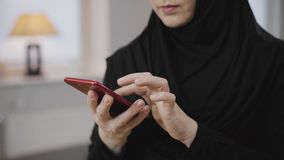 Female hands with beautiful manicure scrolling on smartphone. Young unrecognisable muslim woman in black hijab using