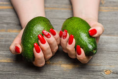 Female hands with beautiful New Year`s manicure keep avocado fruits in style a rustic. Female hands with beautiful New Year`s festive manicure keep avocado royalty free stock photos