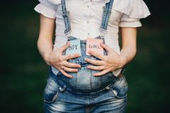 Female hands at belly with with BOY and GIRL cards stock photos