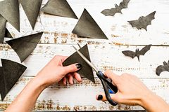 Female hands with black nails cutting halloween flags on white wooden table top view. Halloween concept. female hands with black nails cutting black halloween royalty free stock photography