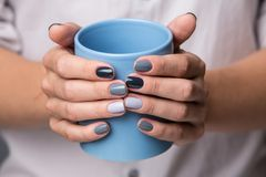 Female hands with blue cup Royalty Free Stock Photo