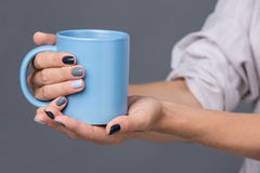 Female hands with blue cup Stock Photo