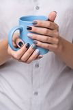 Female hands with blue cup Royalty Free Stock Image