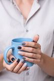 Female hands with blue cup Stock Photography