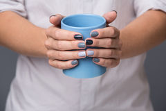 Female hands with blue cup Stock Images