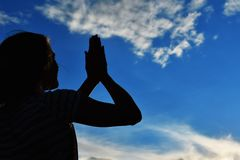 Dark silhouette of female hands at sunset in sky. The palms raised to the sun stock image