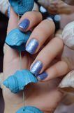 Female hands with blue glitter nail design. Royalty Free Stock Photography