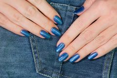 Female hands with blue glossy professional manicure stock photography