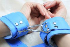 Female hands in blue leather handcuffs. eagerly. Female hands in blue leather handcuffs. on the background sheet. sex toys. passion stock photo