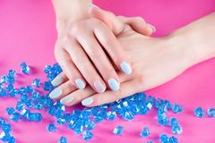 Female hands with blue manicure on finger nails holding hand on many blue crystal or gemstone. Young girl hands with gently blue manicure on finger nails holding stock photography
