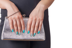 Female hands with blue manicure holding a silver handbag Royalty Free Stock Image