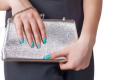 Female hands with blue manicure holding a silver handbag Stock Images