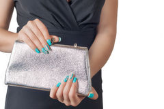 Female hands with blue manicure opening a silver handbag Royalty Free Stock Photo