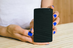 Female hands with blue manicure show a touch screen phone Royalty Free Stock Photos