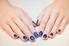 Female hands with  blue nail Polish, close-up Stock Images