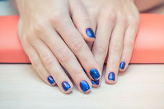 Female hands with  blue nail Polish, close-up Stock Photography